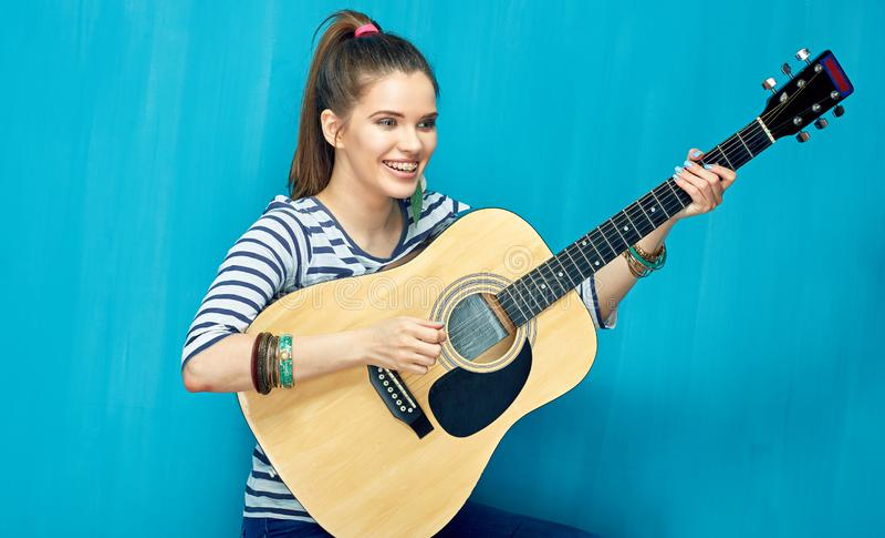 Jeu de l'adolescence de fille avec l'amusement sur la guitare photos libres de droits