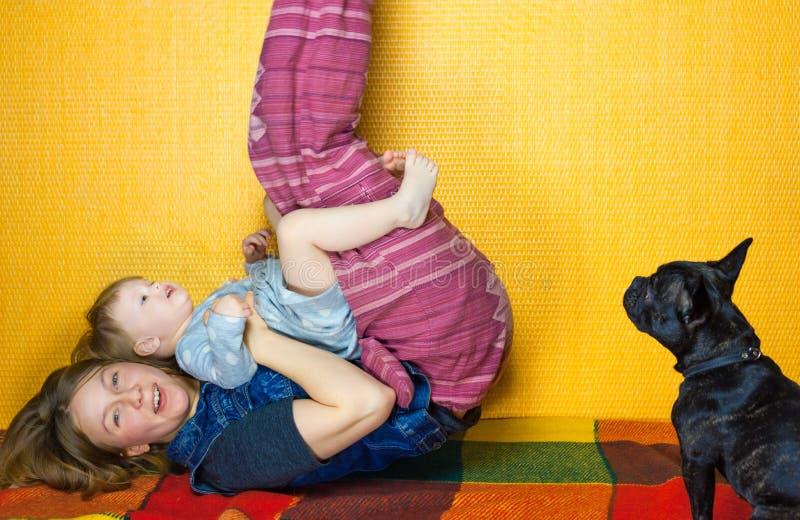 Jeu de mère avec la fille sur le plancher étendez sur le dos la fille et la femme heureuses ont l'amusement, rire la famille appr photographie stock