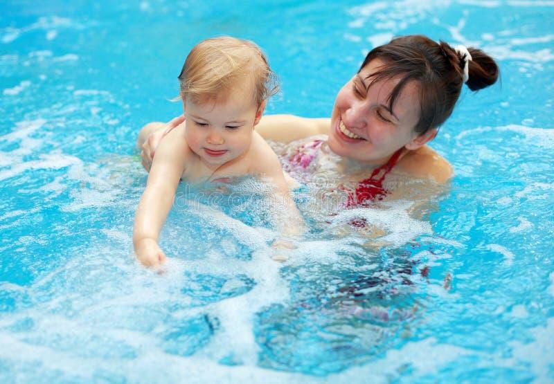 Jeu de mère avec son enfant en piscine photos stock