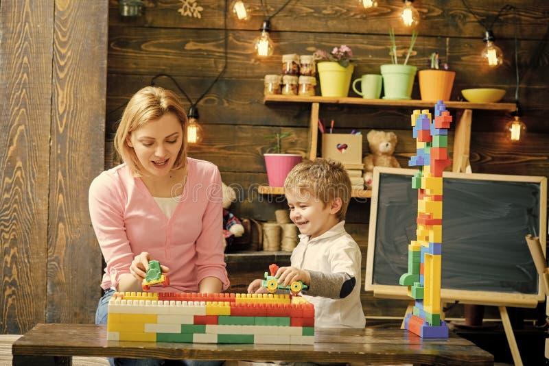 Jeu de mère et de fils avec des blocs de constructeur Maman et enfant emballant avec les voitures en plastique Maman parlant à so photos stock