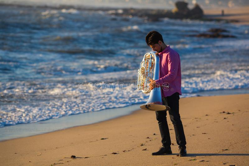 Jeu de musicien au tuba sur le bord de mer romantique détendez image libre de droits
