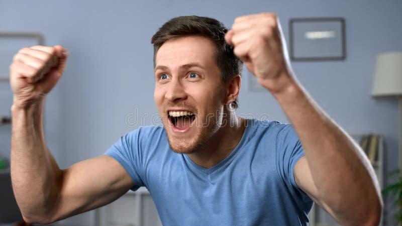 Jeu de observation de fan masculine énergique à TV, équipe de football de soutien, but de réjouissance photo stock