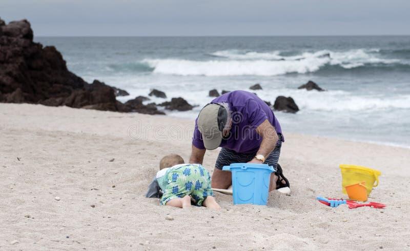 Jeu de petit-fils de grand-père et d'enfant en bas âge sur la plage au Mexique photos stock
