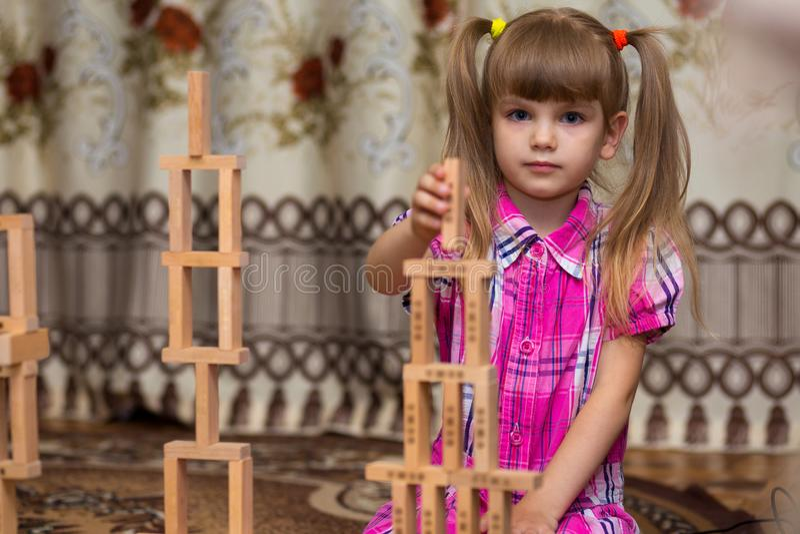 Jeu de petite fille avec les blocs en bois Badinez inspecter les bâtiments en bois de bloc, activités d'enfance photos libres de droits