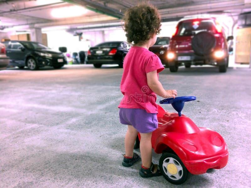 Jeu de petite fille avec une voiture de jouet dans le parking photographie stock