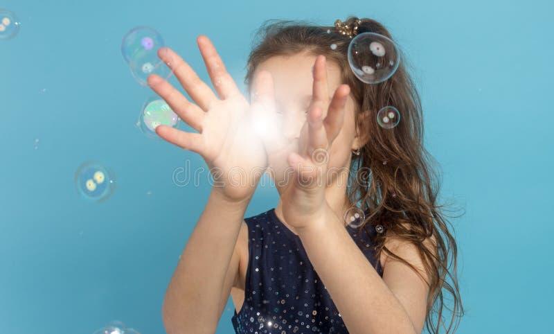 Jeu de peu de fille avec la lumière dans des mains photos stock