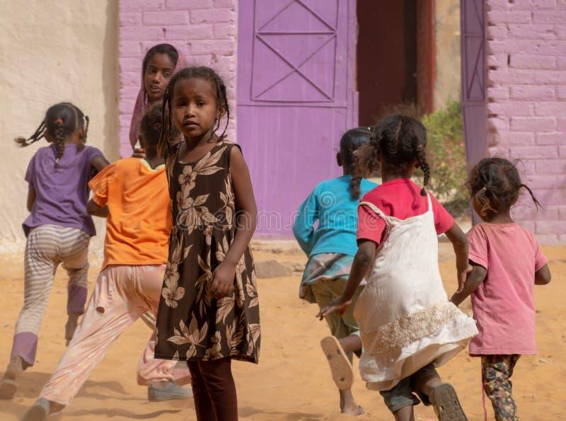 Jeu des enfants devant un jardin d'enfants avec une porte violette en Afrique photo stock