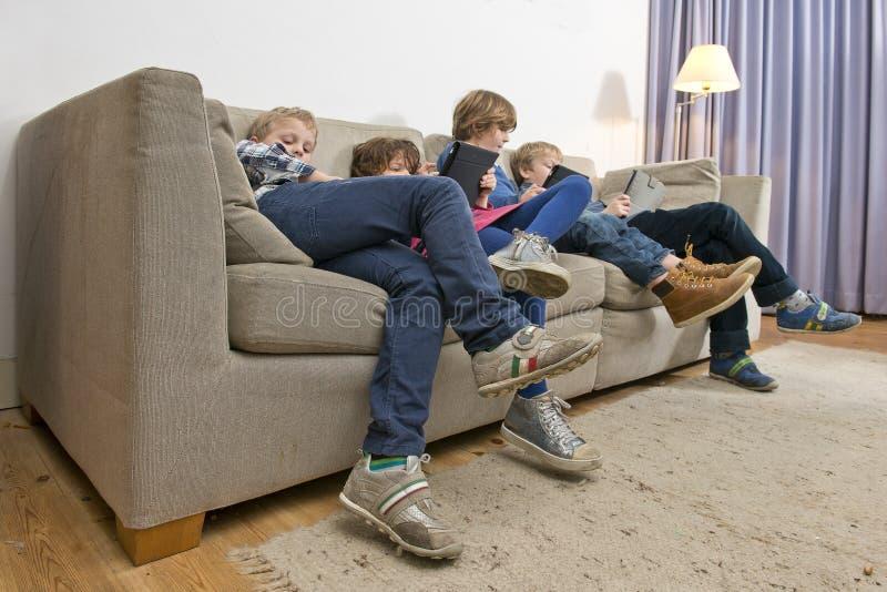 Jeu ennuyé d'enfants sur un divan photo stock