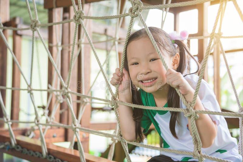 Jeu et sourires de fille dans le terrain de jeu d'école photo stock
