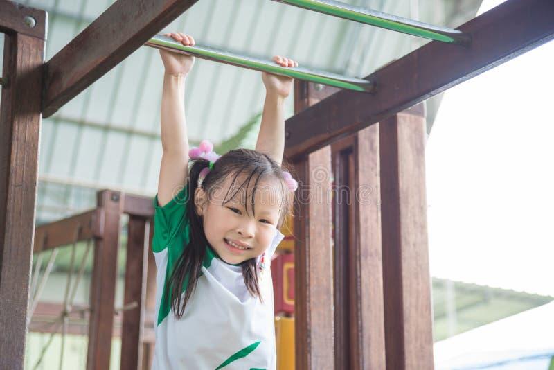 Jeu et sourires de fille dans le terrain de jeu d'école image libre de droits