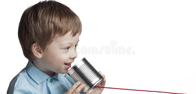 Jeu heureux de garçon dans le téléphone de boîte en fer blanc images stock