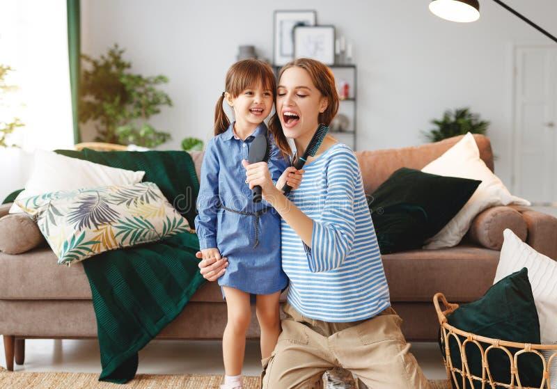 Jeu heureux de mère et d'enfant de famille à la maison et chanter avec des peignes images libres de droits