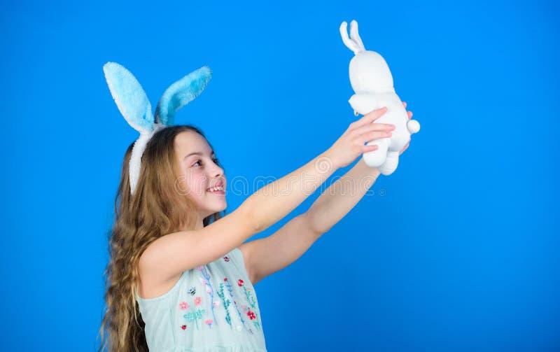 Jeu le jour de Pâques Oreilles de lapin de port de petite fille avec le jouet de Pâques Peu enfant dans le style de lapin de Pâqu photo libre de droits