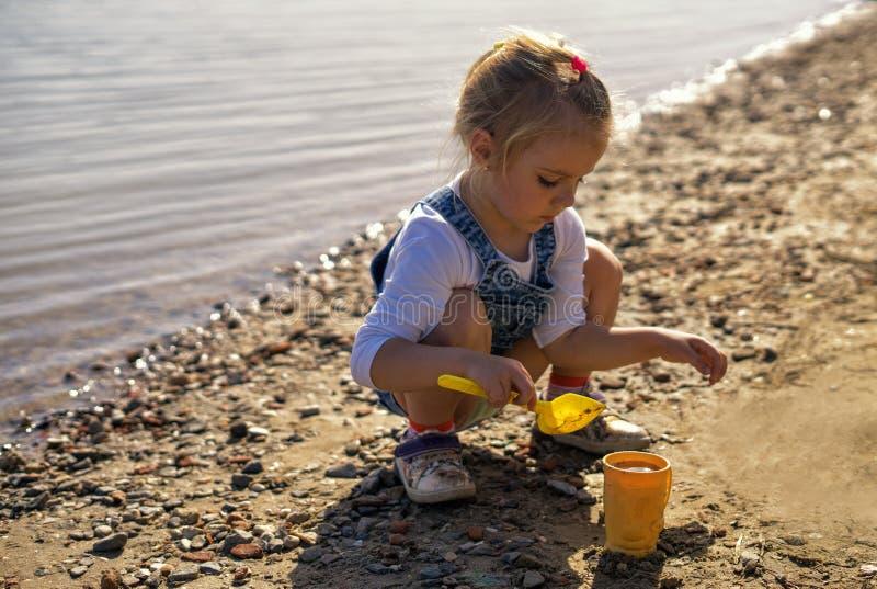 Jeu mignon de petite fille avec le sable et la pelle sur la plage images libres de droits