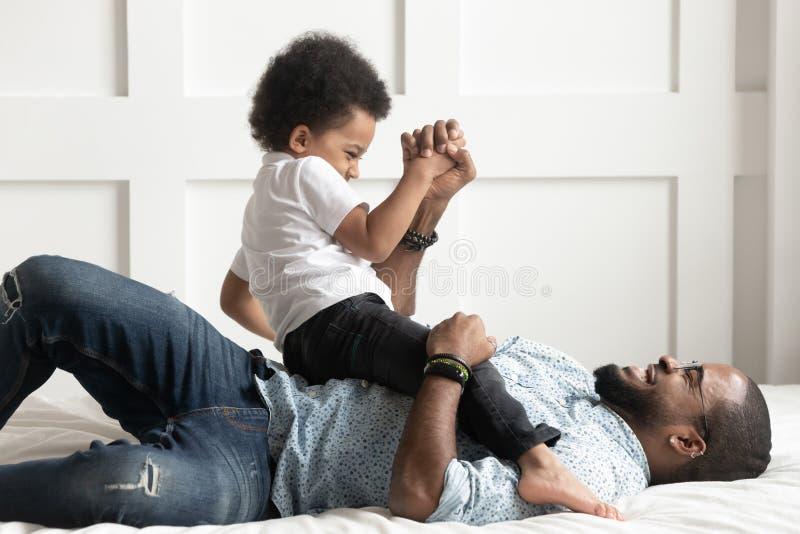 Jeu riant de papa africain heureux avec peu de fils sur le lit photo stock