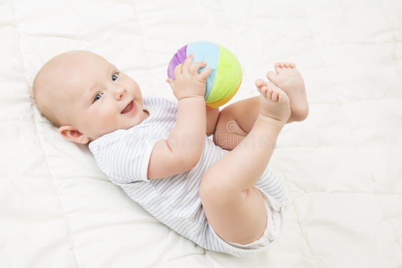 Jeu Toy Ball, enfant heureux de bébé se trouvant sur le dos jouant les jouets mous images stock