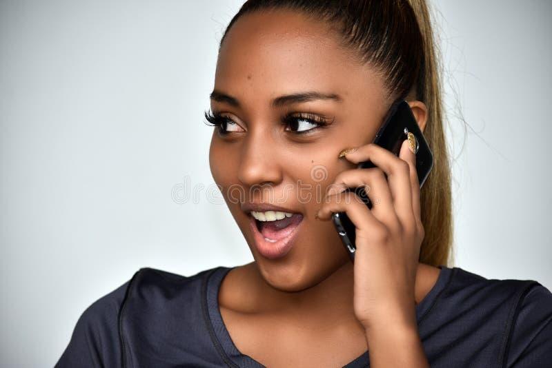 Jeugdig Columbiaans Tienermeisje die Celtelefoon met behulp van en Gelukkig royalty-vrije stock afbeelding