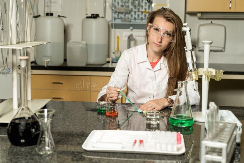 Jeune échantillonnage femelle de technicien de laboratoire avec la solution liquide chimique de pipette dans le laboratoire photographie stock