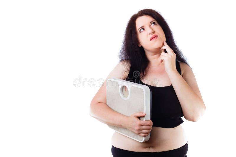 Jeune échelle réfléchie de poids excessif de participation de femme à disposition photographie stock