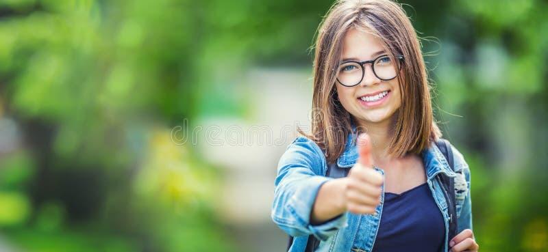 Jeune écolière adolescente attirante montrant des pouces  photo stock