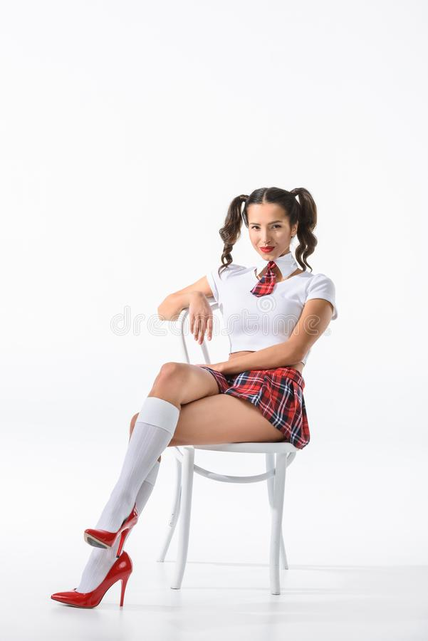 jeune écolière attirante dans la jupe de plaid rouge se reposant sur la chaise photo libre de droits