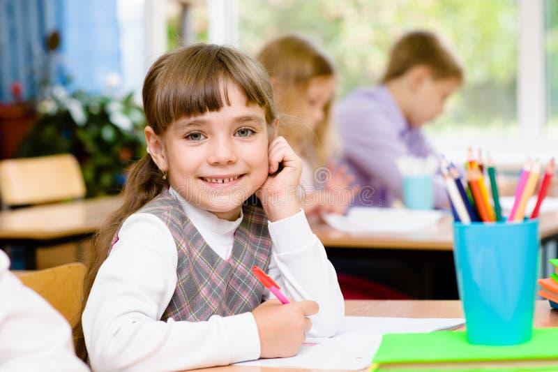 Jeune écolière dans la salle de classe regarder l'appareil-photo photographie stock