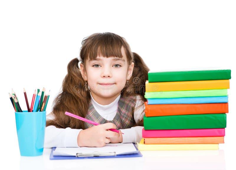 Jeune écolière faisant le travail D'isolement sur le fond blanc photo stock