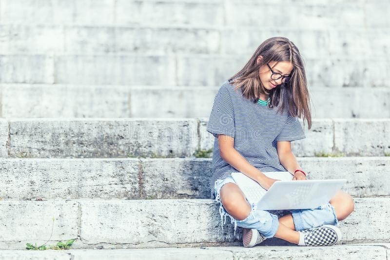 Jeune écolière s'asseyant sur des escaliers avec l'ordinateur portable et le réseau d'Internet ou social de observation images libres de droits