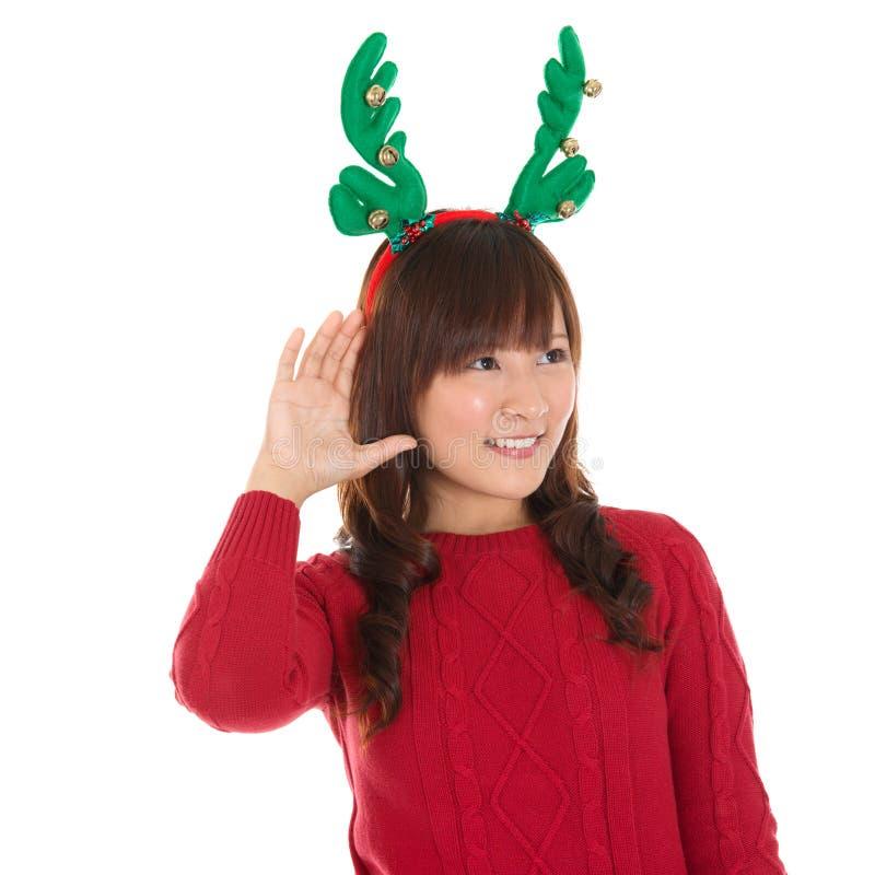 Jeune écoute asiatique de fille de Noël photo stock