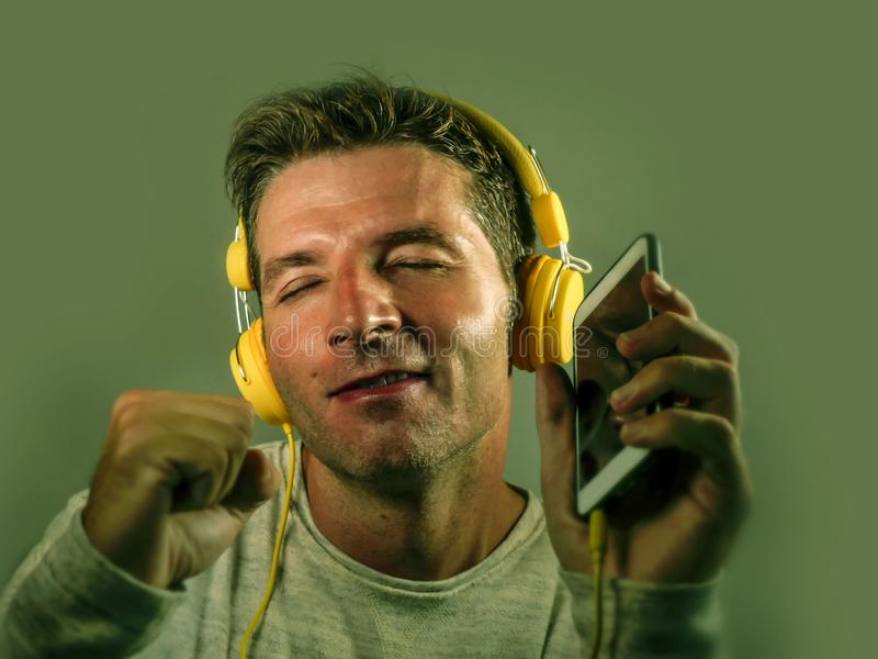 Jeune écouter de sourire d'homme attirant et heureux la musique d'Internet sur des écouteurs tenant le téléphone portable dansant photos libres de droits