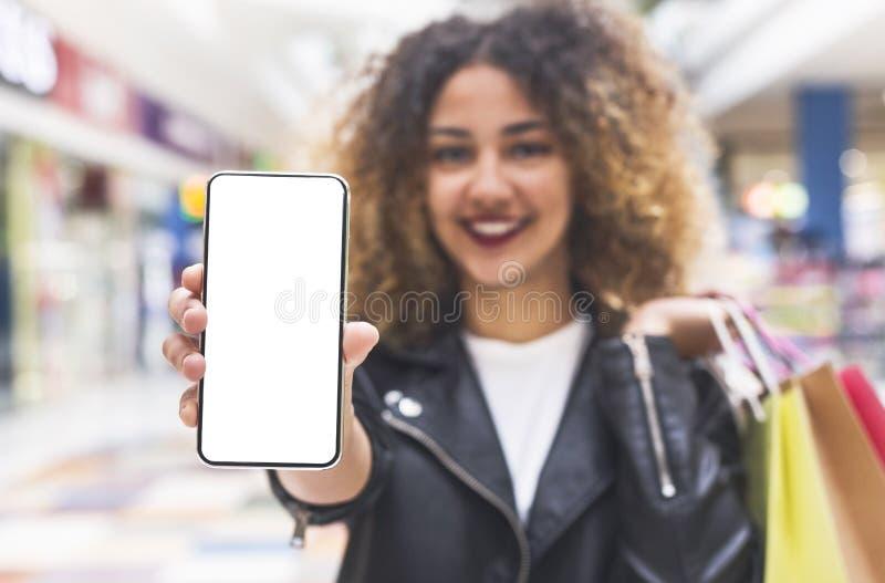 Jeune écran africain de téléphone portable d'apparence de femme avec l'espace vide photos libres de droits