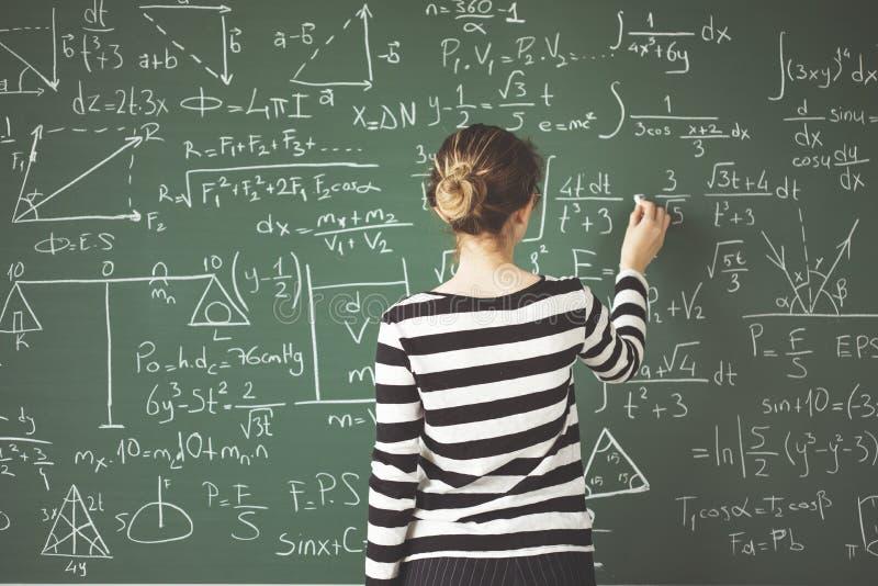 Jeune écriture d'étudiant avec la craie sur le panneau de craie vert dans la salle de classe photo stock