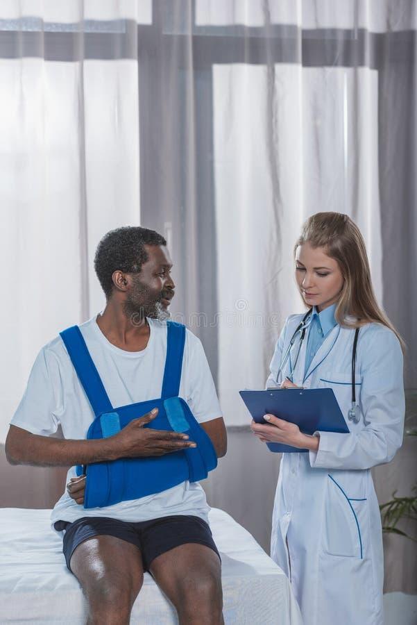 Jeune écriture de docteur quelque chose au presse-papiers au sujet du patient d'afro-américain photographie stock