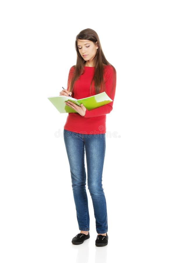 Jeune écriture de femme d'étudiant dans sa note images stock