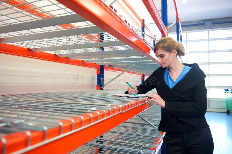 Jeune écriture de femme d'affaires sur le presse-papiers dans l'entrepôt photos stock