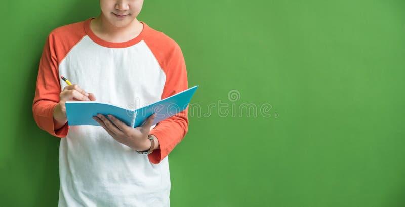 Jeune écriture de garçon d'adolescent sur le carnet bleu se penchant à wal vert photo stock