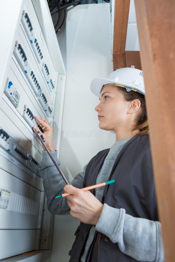 Jeune électricien féminin à l'unité électrique du consommateur photographie stock libre de droits