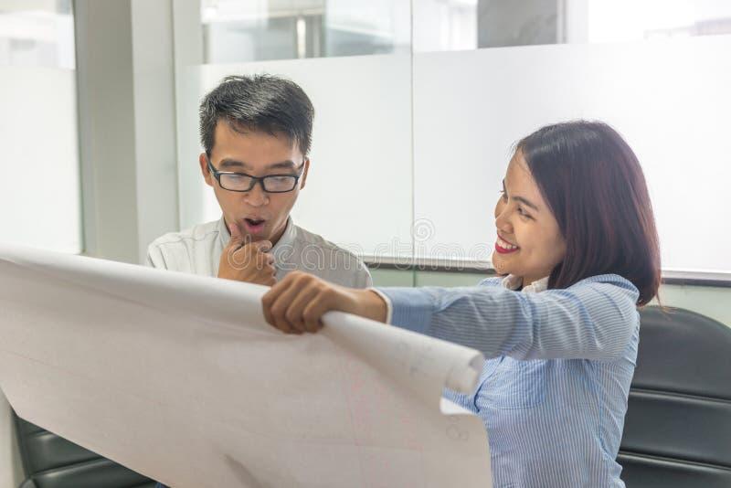 Jeune équipe asiatique d'affaires travaillant et discutant au sujet du nouveau projet image libre de droits