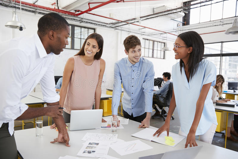 Jeune équipe d'affaires se tenant à un bureau dans le bureau ouvert de plan photos libres de droits