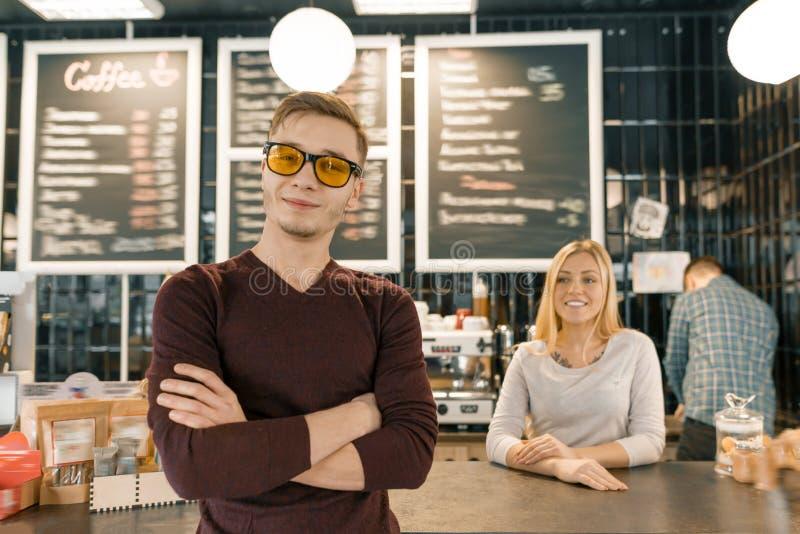 Jeune équipe de trois travailleurs de café, les gens posant et souriant au café près du compteur de barre Travail d'équipe, perso photos libres de droits