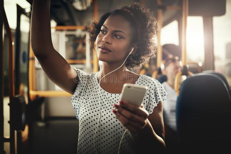 Jeune équitation africaine de femme sur un autobus écoutant la musique photographie stock libre de droits