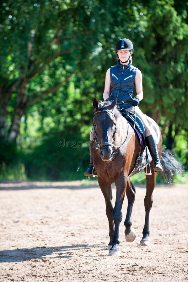 Jeune équitation d'adolescente à cheval à l'école équestre photos libres de droits