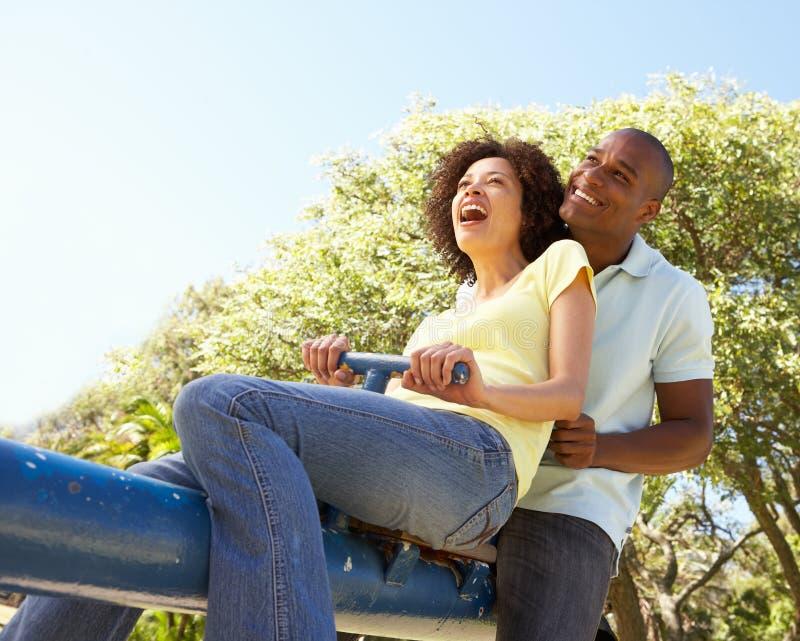 Jeune équitation de couples sur la balançoir en stationnement images libres de droits