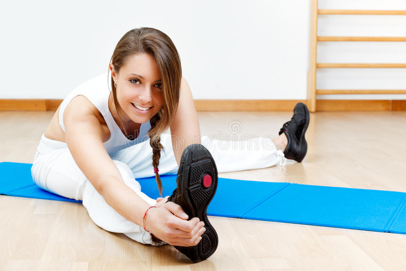 Jeune étirage femelle convenable sur le plancher se reposant sur le tapis image libre de droits