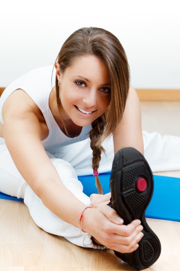 Jeune étirage femelle heureux sur le plancher se reposant sur le tapis image libre de droits