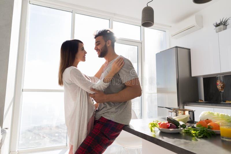 Jeune étreinte de couples dans la cuisine, l'homme hispanique et l'étreinte asiatique de femme photographie stock libre de droits