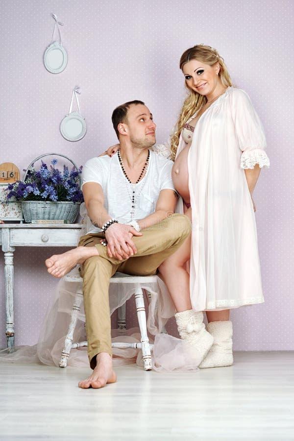 Jeune étreinte enceinte heureuse de couples dedans images stock