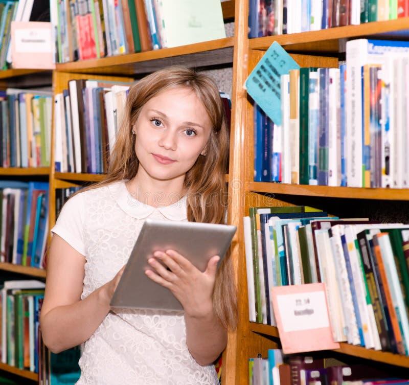 Jeune étudiant à l'aide d'une tablette dans une bibliothèque image libre de droits
