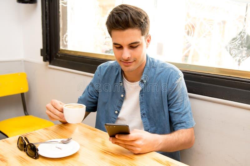 Jeune étudiant à l'aide de son téléphone intelligent pour lire le texte tout en ayant un café images libres de droits
