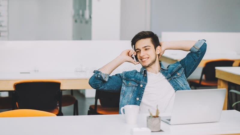Jeune étudiant élégant avec la barbe travaillant sur l'ordinateur portable photographie stock